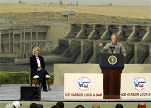(AP: Ted S. Warren) President Bush speaks at the Ice Harbor Lock and Dam near Burbank, Wash. Friday, Aug. 22, 2003 as Secretary of the Interior Gale Norton looks on at left. Bush was in the state to address environmental and salmon issues.