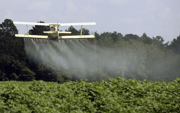 An aerial applicator sprays a field. Oregon regulators are proposing a rule to limit the use of chlorpyrifos. (Associated Press photo)