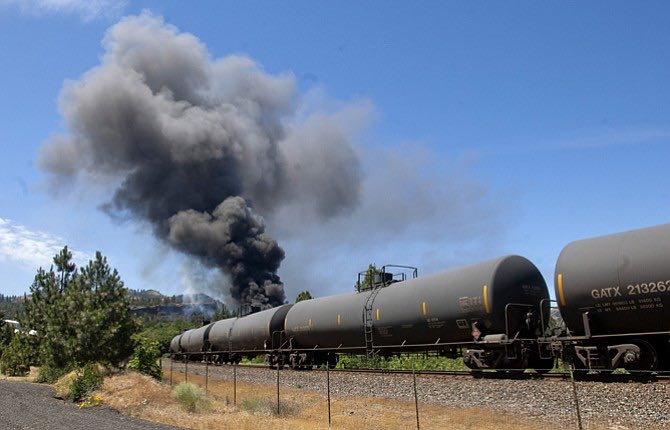 A train carrying Bakken crude oil, a type of oil known to be highly volatile, sits alongside a public parking area in downtown Mosier after derailing and catching fire around noon on Friday. (Mark Gibson photo)