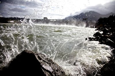 (Jamie Francis) Water from The Columbia River splashes high as it meets rocks on shore just below Bonneville Dam.