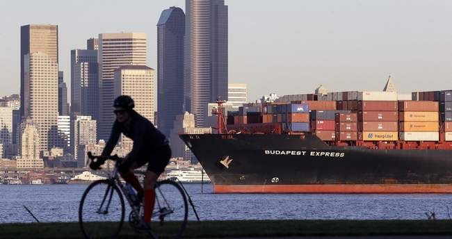 A bicyclist rides in view of a loaded container ship anchored in Elliott Bay near downtown Seattle in 2014. With a second major carrier all but pulling out of the Port of Portland, there's concern that business will move to Seattle, increasing costs. (AP Photo)
