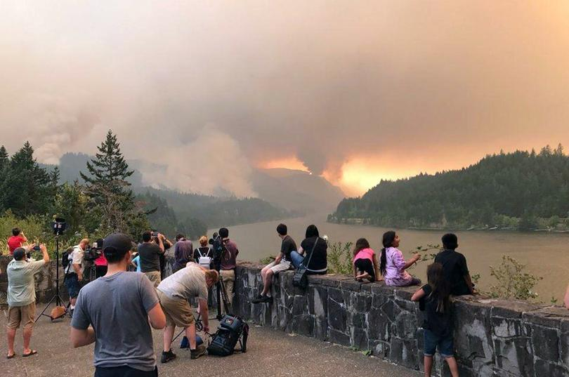 This Sept. 4, 2017, photo provided by Inciweb shows people at a viewpoint overlooking the Columbia River watching the Eagle Creek wildfire burning in the Columbia River Gorge east of Portland. (Inciweb / Associated Press)