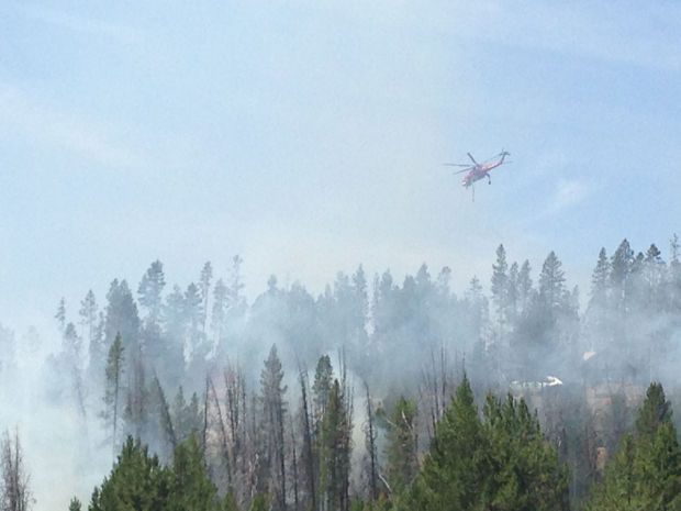 (Kimberlee Kruesi photo) A helicopter flies over the #210 Road Fire near Redfish Lake Tuesday, July 23.