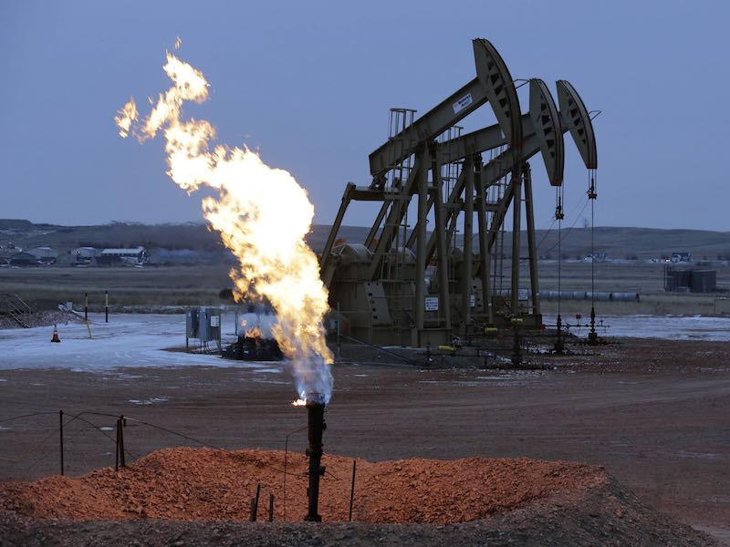 Oil pump jacks work behind a natural gas flare near Watford City, N.D., in 2014. The oil and gas industry is lobbying lawmakers to repeal a rule that aims to limit the emissions of methane, the chief component of natural gas.