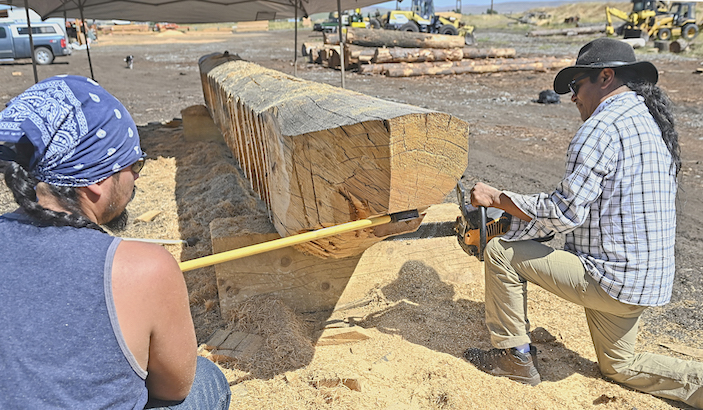 INez Perce tribal members Allen Pinkerton Jr., right, and Adam Capetillo, work to perfect the bow angle on a dugout canoe Saturday, Aug. 8. The canoe is being made from logs donated by JZ Lumber Co., of Joseph. The two started work on the craft at JZ Lumber's property in Joseph.