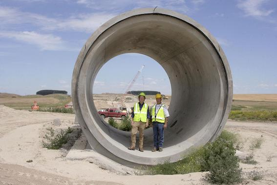 East Columbia Basin Irrigation District engineer Nate Andreini and John McCourtie, assistant manager of operations and maintenance, show the size of the siphons built for the East Low Canal June 26 near Othello, Wash.
