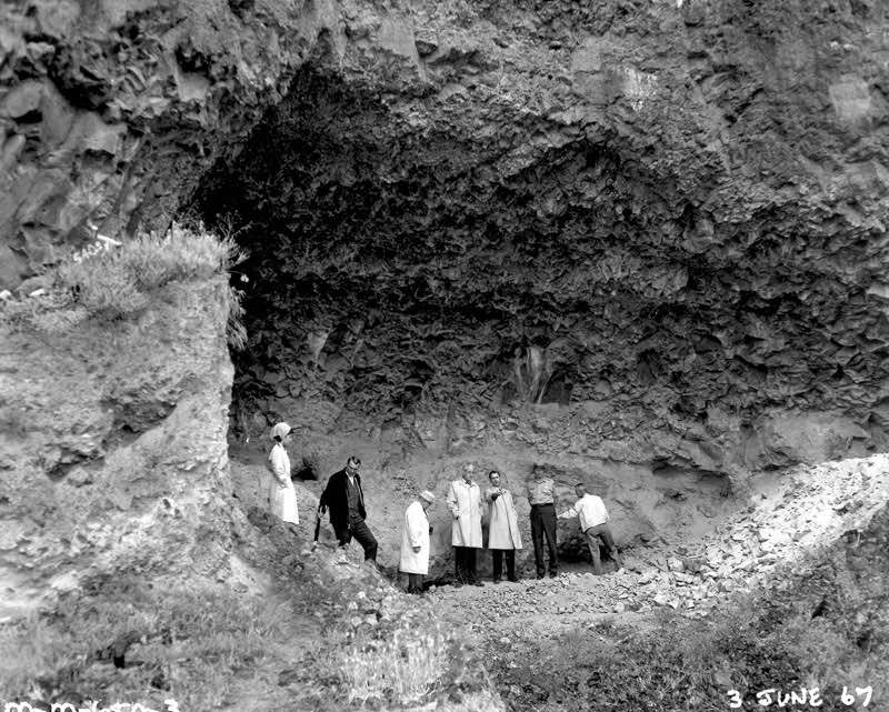 Unknown officials at the Marmes Rock Shelter in Franklin County, Washington. In 1969, the site was submerged in water when a levee protecting it from waters rising behind the then newly constructed Lower Monumental Dam, which was 20 miles (32 km) down the Snake River, failed to hold back water that leaked into the protected area through gravel under the soil,[4] creating Lake Herbert G. West. (ACOE photo)