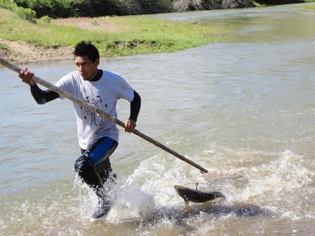 Ethan Thomas, a Shoshone Paiute fishermen, races to shore with a freshly caught chinook salmon from the Owyhee River on the Idaho Nevada border. Tribal leaders held a spearing workshop the night before the fish were released to help tribal members learn the traditional methods of fishing salmon. (SHOSHONE PAIUTE FISHERIES photo)