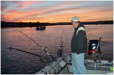Boat angler watches pole for a strike while salmon fishing.