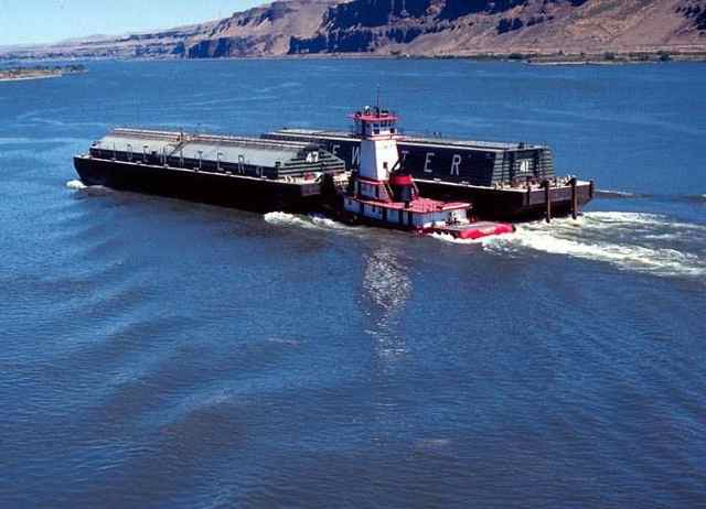 Tug pushes a wheat barge on a Lower Snake River reservoir.