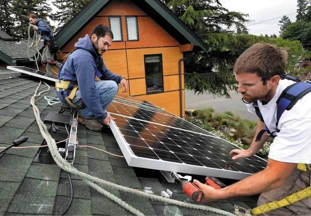 (Drew Perine photo) South Sound Solar employees from right Aaron Bonfield, Daniel Kuni and Brian Jones install one of 10 Itek solar panels on the roof of an Olympia home.