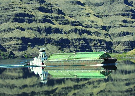 Wheat barge on the Lower Snake River, likely near the entry of Lower Granite dam's lock for transport of wheat downstream.