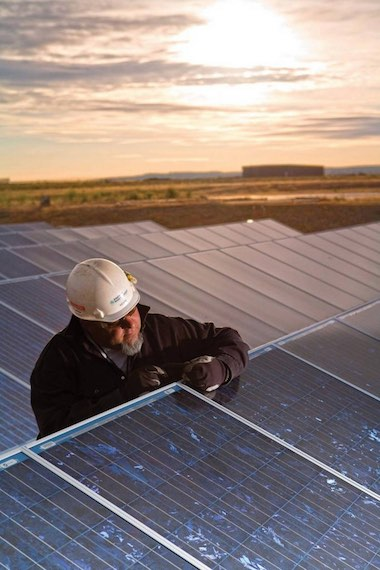 A worker checks solar panels at the White Bluffs Solar Station near Richland. A French firm is set to build a new solar station near the site. File Caren Brinkema