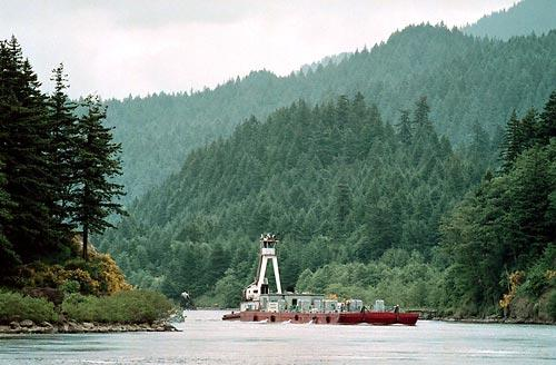 A juvenile-fish transport barge rounds a bend in the Columbia River near Bonneville Dam in this June 1999 photo. A federal judge yesterday ordered more water spilled this summer at four federal dams along the Snake and Columbia rivers in an effort to boost an endangered run of chinook salmon.