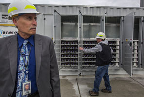 (Steve Ringman photo) Snohomish PUD Chief Executive Steve Klein says the huge lithium-ion battery system behind him can store enough energy to power 400 families for an hour. PUD foreman Scott Westphal opens doors to the inner workings, housed in a former shipping container.