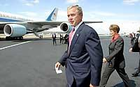 (John Lok) President Bush heads to a podium yesterday on the runway at Boeing Field after meeting for about 30 minutes with six local business leaders.