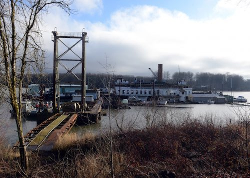 Coast Guard responders from Sector Columbia River Incident Management Division begin a proactive cleanup effort of the barge Multnomah, which is moored at a site along the Columbia River, Goble, Ore., Feb. 2, 2016. The Coast Guard opened the Oil Spill Liability Fund to remove hazardous materials, from the Multnomah a 265-foot barge, in order to mitigate a substantial threat to the environment.