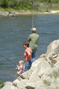 (Willy Cook) Four-year-old Hailey angler Alexis Burk, standing next to Gaylynn and Rick Burk, fishes for chinook salmon along the upper Salmon River downstream of Stanley last Saturday. Like the few other anglers who have taken to the river for the first chinook season along the scenic stretch of river in 31 years, the Burks reported no success. Fish and Game fisheries biologists believe high spring flows are keeping the salmon holding downstream.