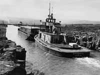 (OREGON STATE ARCHIVES, OREGON DEPARTMENT OF TRANSPORTATION, OHD5572) Grain barge in the Celilo Canal at The Dalles, 1953.