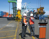 Gov. Ted Kulongoski, left, and Port of Portland Executive Director Bill Wyatt talk prior to a ceremony July 19 in which the state handed the port a $7.5 million check for the purchase of a fourth Post-Panamax crane