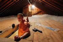 Stephen Botelho stands in the entrance to his attic, at his Westwood, Mass., home. Botelho has installed cellulose insulation to the attic as an energy saving measure. (Steven Senne/AP Photo)