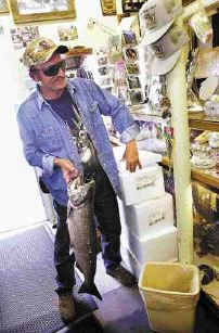 Huck Eckes, of Devil's Lake, North Dakota, proudly displays a 13.5-pound Salmon that he caught earlier in the day. Eckes, who has fished for salmon almost everywhere that a person can, considers himself a 'fishing machine.'