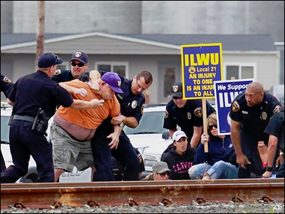 (Bill Wagner) Law enforcement personnel wrestle ILWU Local 21 longshoreman Kelly Muller to the ground as they arrest protesters and try to clear the tracks at the Port of Longview Wednesday.