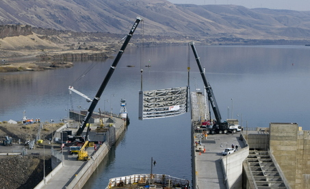 (Brent Wojahn) Cranes lift replacement gate into position at John Day Dam's navigation lock.
