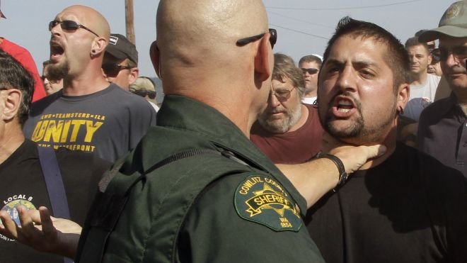A Cowlitz County Sheriff grabs a union worker by the throat as police move in on several hundred union workers blocking a grain train in Longview, Wash., Wednesday, Sept. 7, 2011