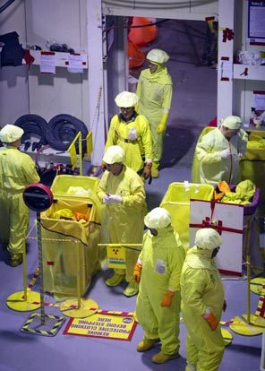 (Steve Ringman, Seattle Times) A worker, top, checks a gauge in the Columbia Generating Station control room that shows the status of the fuel core. Below, workers on a shift change at the plant near Richland remove their protective clothing before moving outside the roped-off containment area.