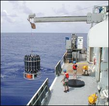 (Christopher Sabine, NOAA) Scientists lower 36 bottles used for water sampling from the deck of the Thomas G. Thompson while doing research near the equator.