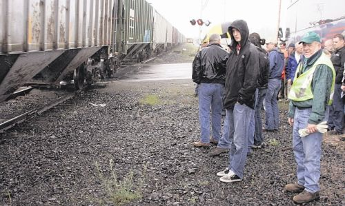 Participants in the Washington Association of Wheat Growers legislative tour watch in the rain as a train goes by the afternoon of May 23 on a road crossing near Medical Lake, Wash. Wheat growers and state representatives say the poor condition of the state-owned railroad needs to be addressed. (Matthew Weaver photo)