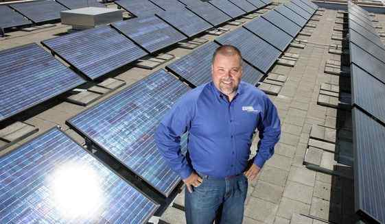 In this July 29, 2011, file photo, Mark Stokes, manager of Idaho Power's power supply planning, poses for a photo on the roof of the agency's downtown Boise, Idaho building where a solar array has been gathering energy.