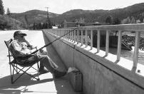 Vic Bruderer, of Spokane, fishes for Salmon off a bridge in Orofino on Friday.