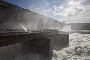 (Jamie Francis) Water powers through the spillway at The Dalles Dam. Two years ago, the Army Corps of Engineers spent $51.3 million to build an 850-foot-long wall just past the spill outlets -- the light-gray wall in the background -- to divert young migrating fish from predators, smallmouth bass and pikeminnow that congregate in shallow water just downstream. The wall helped boost juvenile salmon and steelhead survival at the dam to more than 90 percent.