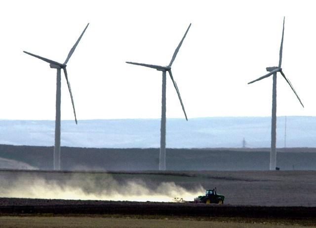 Wind turbines tower over a tractor and plow tilling farmland near Wasco, Ore., March 4, 2002. (Don Ryan AP photo)